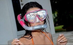 Latina 18-19 y.o. takes orange swimsuit and poses with diving mask and flippers