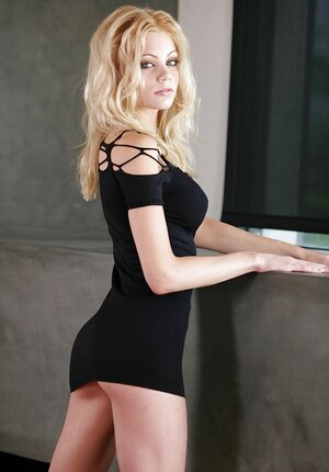 Girl wears slinky black dress and blatantly pulls it up a bit flashing buttock