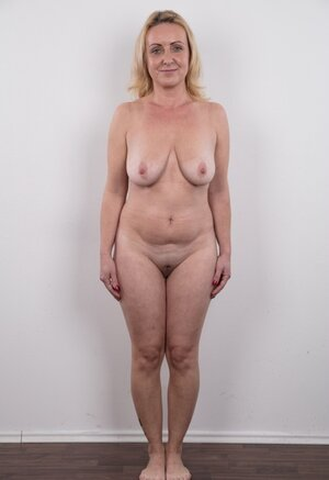 Dirty old woman has saggy breasts and also belly but still poses naked in studio