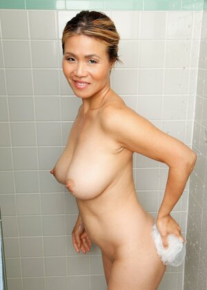Oriental female with awesome natural tits combines taking shower with photo session