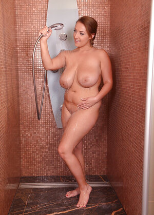 Red-haired diva with natural milk sacks smiles while massaging sissy in shower
